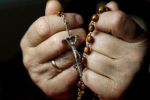 mani-di-donna-che-prega-e-rosario